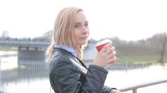 Beautiful girl drinking coffee on the street looking at the camera Stock Footage