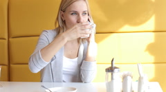 The girl stir and drink tea and speaks by phone in cafe. Stock Footage