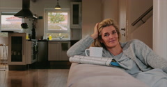 Housewife taking a relaxing break on sofa - stock footage