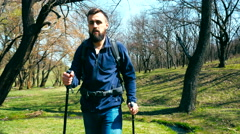 Young hiker with a backpack and trekking poles walks outdoor Stock Footage