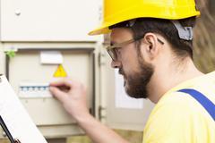 Electrician checking fuse box Stock Photos