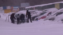 The guys are pushing a car stuck in the snow Stock Footage
