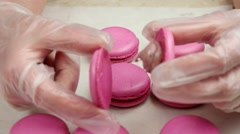 Two halves of pink Macaroon in the hands of chief Stock Footage
