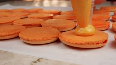 Orange Macarons halves coated with cream Stock Footage