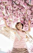 Young caucasian woman is jumping under the flowering sakura tree - stock photo