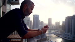 Expat man messaging on mobile at balcony. Stock Footage