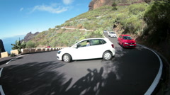 Vehicles pass extremely curved turn on mountain hairpin road TF-436. Masca Stock Footage