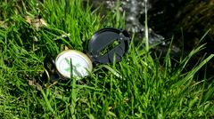 Compass on the grass near litle stream - stock footage