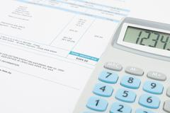 Unpaid utility bill and calculator over it series Stock Photos