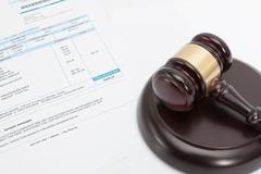Unpaid bill with wooden gavel over it series Stock Photos
