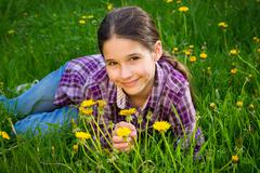 Cute girl on field with dandelions - stock photo