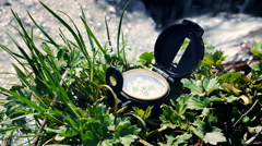 Compass on the grass near litle stream Stock Footage