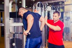Personal trainer helping men working out in weights room at the gym - stock photo