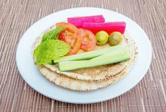 Brown pita bread  with sliced cucumbers,olives,tomatoes on a white plate - stock photo