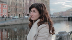 Sad beautiful woman standing near the river in the old city - stock footage