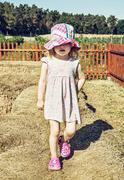 Little girl is walking on the haystack Stock Photos