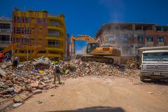 Portoviejo, Ecuador - April, 18, 2016: Heavy machinery picking rubble from Stock Photos