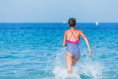 Girl running through the water - stock photo