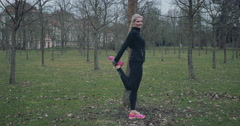 Fit middle-aged woman stretching in park Stock Footage