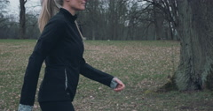 Torso of a woman out jogging in a park - stock footage