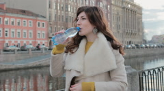 Attractive girl drinks water from a bottle in the old city center near the river Stock Footage