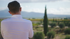 Young man buttons his shirt on the terrace. Stock Footage