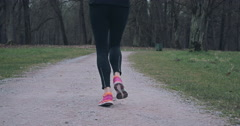 Sporty woman jogging along a rural road Stock Footage