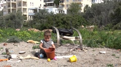 Child plays with disposals on sand near dump  Stock Footage