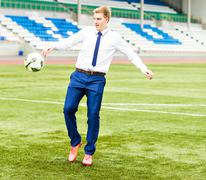 European Football Championship concept. Businessman playing soccer ball - stock photo