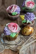 Cupcakes with floral decor. - stock photo
