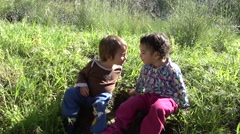 Little boy and girl exchange glances and kiss Stock Footage