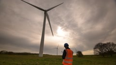 An official checks over a large Wind Turbine - stock footage