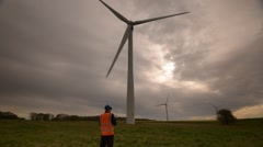 A large Wind Turbine inspected by an engineer Stock Footage
