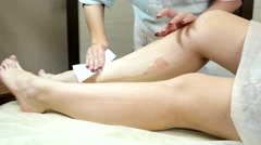 Unwanted Hair on my legs pulled strip wax beautiful girls feet. - stock footage