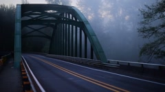Vehicle Driving Across Bridge Early Morning In Fog Stock Footage