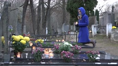 young woman kneel on tomb mother grandmother put candle and pray. 4K - stock footage