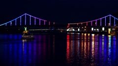 Ship sails with lights of night city and bridge with reflections on the river Stock Footage