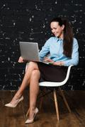 Portrait of elegant dressed brunet woman sitting in loft apartment and working Stock Photos