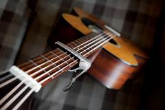 Acoustic guitar neck with a capo - stock photo
