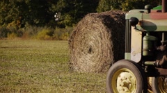 Rolled grass next to an old rusty farm tractor on a hot day. Stock Footage