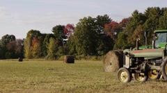 Rolled grass next to an old rusty farm tractor on a hot day. - stock footage