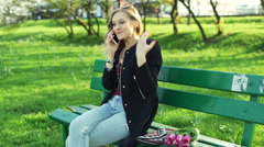 Girl talking on cellphone in the park and looking surprised - stock footage