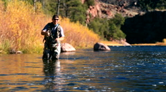 Man in river casting fly rod upstream Stock Footage