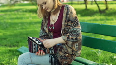 Girl improving her makeup while sitting in the park, steadycam shot Stock Footage