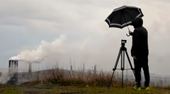 Man Photographer Closes the Camera on a Tripod Umbrella From the Rain and Wind. - stock footage