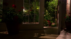 Dark room with an open French door leading to the illuminated patio. Stock Footage