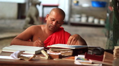 Asian monk in red clothes writes annals Stock Footage