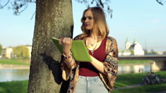Girl standing in the park and drawing something in her sketchbook Stock Footage