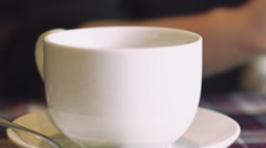 Close up female hand stirring cup of coffee. Slowly Stock Footage