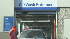 Cars line up at an automated car wash entrance Stock Footage